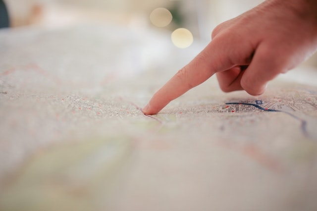 Person pointing at Outstanding Brandings location on a map