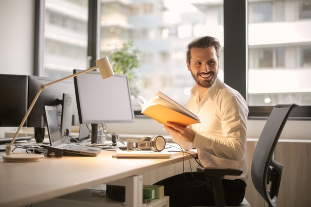 man at desk smiling