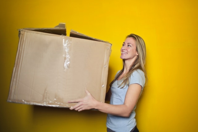 woman holding a box on a yellow background